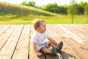 Summer, childhood and baby concept - little boy having fun in summer nature.