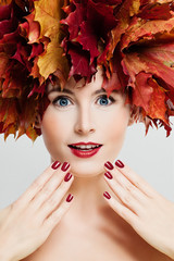 Autumn Makeup. Beautiful Woman with Fashion Makeup, Manicure Hands and Fall Leaves Wreath. Face Closeup