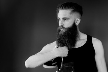 black and white profile of bearded man. Hands holding sneakers.