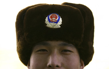 A paramilitary policeman wears a warm hat bearing the Chinese police badge in central Beijing