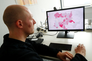 Data visualiser Hans Hack poses at his desk in front of a computer screen showing Aleppo's destruction projected on a Berlin map, in Berlin