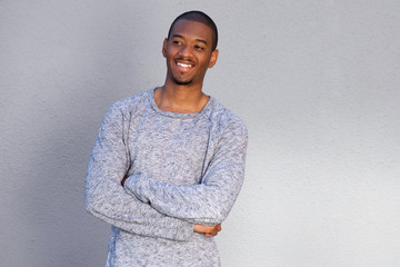 smiling young african man standing against gray wall with arms crossed