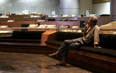 Investor sits as he monitors share market prices in Kuala Lumpur