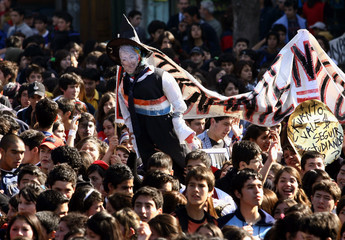 High school students hold an effigy of Chile's President Bachelet during a protest in Valparaiso