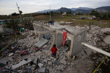 Residents stand next debris after fireworks stored in a house exploded in San Isidro