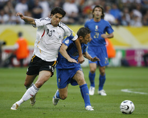 Germany's Ballack battles for the ball with Italy's Totti during their World Cup 2006 semi-final soccer match in Dortmund