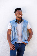 smiling young black man standing by white wall with head phones