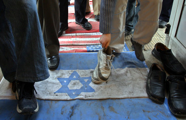 Organizers place flags on the pavement leading up to a mosque in Damascus