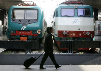 Woman walks past trains at Termini station in Rome