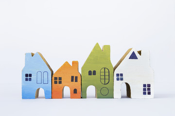 Colorful wooden miniature house on white background, business property real estate concept