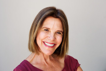 Close up attractive middle age woman smiling against gray wall