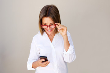 businesswoman with glasses looking at cellphone