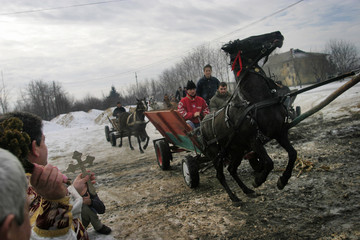 Romanian Orthodox priest blesses horses and passengers in a cart in Rovine