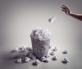 Throwing paper ball in the waste paper basket or office bin