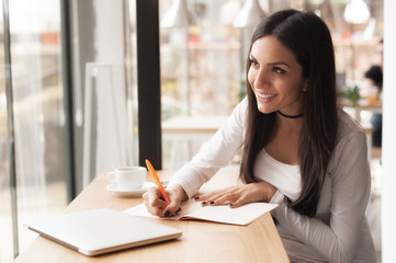 Young woman writing in her notebook and drinking morning coffee