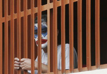 A Peruvian inmate with his face painted as a joker watches from behind bars after a ceremony marking Resocialization Day at the Castro Castro prison