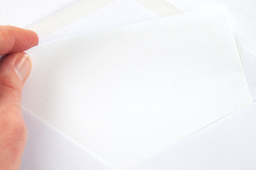 hand pulling blank sheet of paper from white envelope, white background
