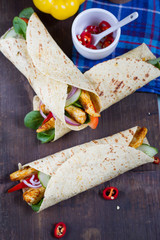 Fajitas with chicken and vegetables. Fajitas, tortillas, wraps on wooden board. Blue background and vegetables.