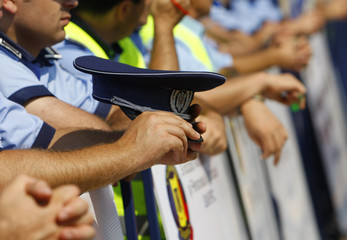 A policeman holds his hat during a protest of the policemen trade union in front of Victoria palace in Bucharest
