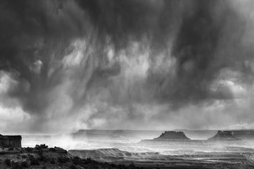 Usa, Utah. Canyonlands National Park. Black and white image of approaching rainstorm from canyon overlook, Island in the Sky