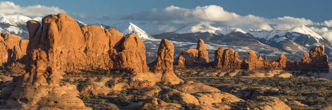 Usa, Utah, Red rock formations of the Windows Section with clouds and snow on the La Sal Mountains, Arches National Park