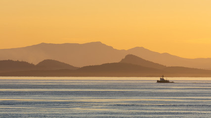 View of tugboat moving on sea with mountains in background at sunset