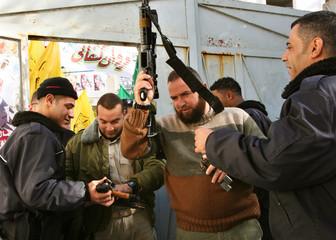 Palestinian policemen surrender their guns outside polling station in Gaza
