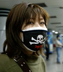 A Chinese commuter wearing a skull and crossbones protective face mask waits for a ride at a Shangha..