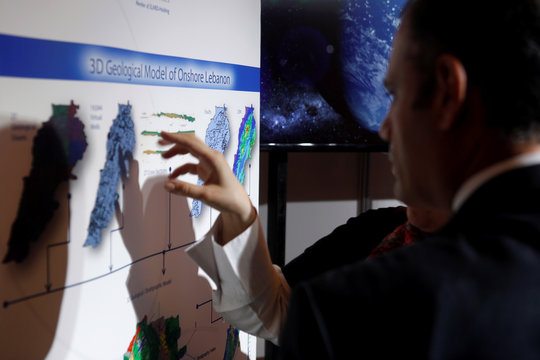People inspect maps of Lebanon during the third Lebanon International Oil and Gas Summit in Beirut
