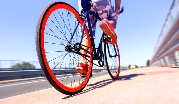 Man cycling on sport bike - Bicycle wheels and road perspective with cyclist riding  blue summer sky background - Concept of alternative transportation  environmental friendly