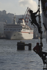 Trainees climb a rope ladder costumed as pirates during an anti-piracy drill at the port of Haifa