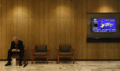 A man takes a seat next to a monitor showing Nikkei average at a securities firm in Tokyo