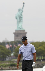 New York's Statue of Liberty is seen in the background as Tiger Woods of the U.S. walks up the 18th fairway during first round play at The Barclays golf tournament