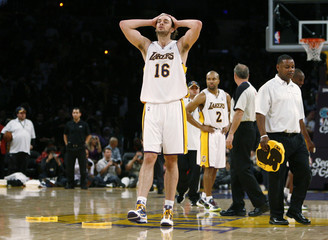 Los Angeles Lakers' Gasol and Fisher react as a man picks up a foam hand after fans threw them onto the court against the Cleveland Cavaliers in Los Angeles