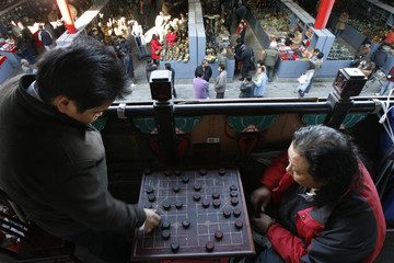 Two men play traditional board game at Panjiayuan in Beijing