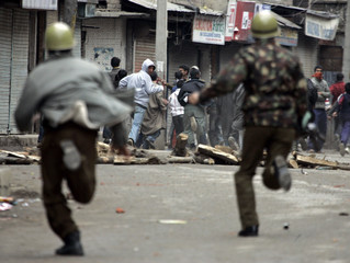 Indian policemen chase away Kashmiri protesters during protest in Srinagar