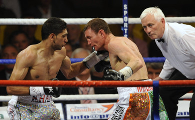 Britain's Amir Khan lands a punch on compatriot Michael Gomez during their Commonwealth lightweight title boxing match in Birmingham
