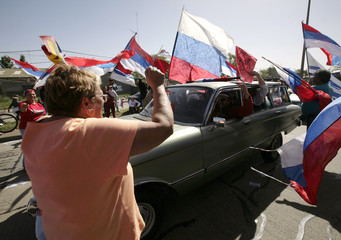 Supporters of Uruguayan party Frente Amplio cheer for Uruguayans living in Argentina as they arrive home to vote in presidential elections, in Montevideo