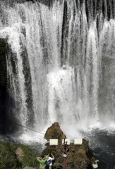 Tourists take pictures of the waterfalls where the Rivers Vrbas and Pliva meet in the centre of the northern Bosnian town of Jajce