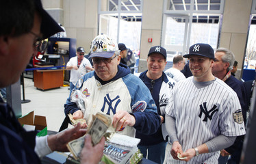 New York Yankees fans buy game programs at the new Yankee Stadium before the first regular season MLB baseball game between the Yankees and the Cleveland Indians in New York