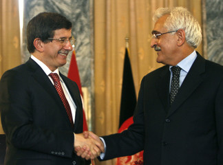 Afghanistan's Foreign Minister Spanta shakes hands with his Turkish counterpart Ahmed Davutoglu during a news conference in Kabul
