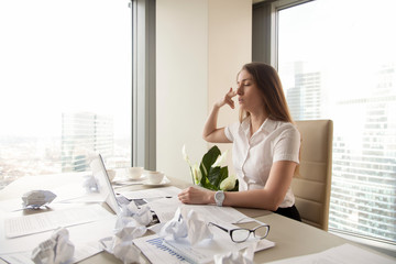 Tired businesswoman puts finger gun to head, crumpled paper covered desk. Female employee wants kill herself at workplace. Figuratively suicide because of chronic fatigue, too much work stress concept
