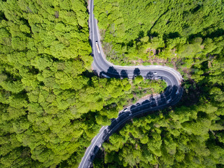 Forest curved road with trucks and cars on it. Aerial view from a drone.