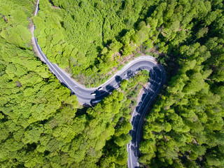 Winding forest road with cars on it. Top down view from a drone
