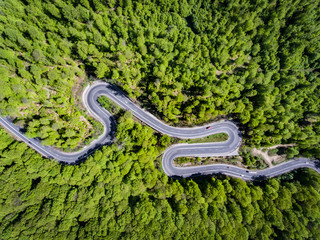 Winding road in the forest. Transylvania, Romania, Europe. Cars passing on road.