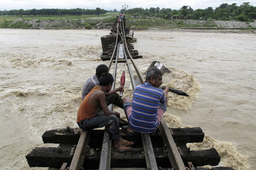 People look at a railway bridge on the Balason River which was partly washed away by heavy monsoon rains in Matigara village