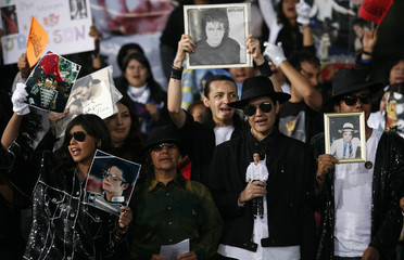Mexican fans of the late pop star Michael Jackson hold pictures during a tribute in Mexico City's main square Zocalo