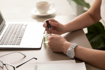 Photo of womans hand on desk with laptop making manicure. Businesswoman painting nails or applying varnish at office. Female office worker procrastinating or bored at workplace