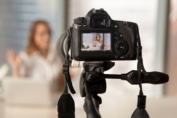 Close up image of camera on tripod with smiling woman on back screen and blurred scene on background. Recording video on modern DSLR camera. Personal videoblog social network concept