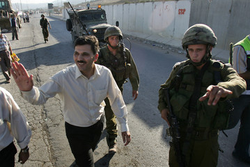 Palestinian Deputy Prime Minister al-Shaer gestures as he escorted by Israeli soldiers through the Hawara Checkpoint near Nablus